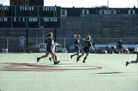 Augsburg women's soccer players run across the athletic field, October 1987