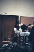 Augsburg women's basketball player takes drink from water bottle, February 1988