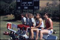 Augsburg women's softball players sitting on a bench, May 1988