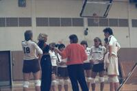 Augsburg women's volleyball players form circle around coach, October 1987