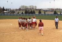 Augsburg women's softball players huddle together, May 1988