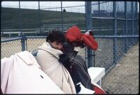 Augsburg women's softball players bundled in blankets, May 1988