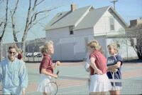 Augsburg women's tennis player talking with teammate and rival players, April 1988