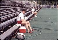 Augsburg track and field team runner sitting on bleachers, April 1987