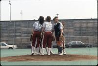 Augsburg women's softball players huddled at pitcher mound, April 1987