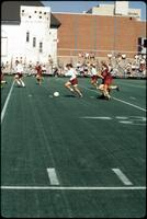 An Augsburg women's soccer team player dribbles forward with the ball, 1989.