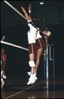 Augsburg women's volleyball team players jump up to block a shot, 1989.