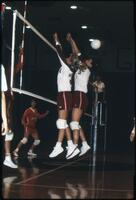 Augsburg women's volleyball team players jump up to block a rival, 1989.