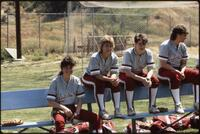 Augsburg women's softball team players sit on the bench and support their teammates, 1989.