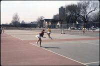 An Augsburg women's tennis team player does an acrobatic move to hit the ball, 1989.