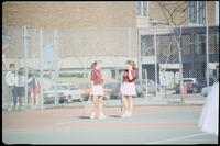 Augsburg women's tennis team players play doubles in a match, 1989.