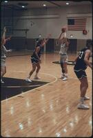 An Augsburg women's basketball team player attempts to pass a ball to a teammate, 1989.