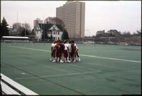 Augsburg women's softball team players huddle up at the athletic field, 1990.