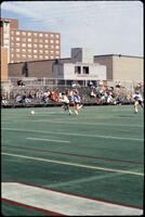 An Augsburg women's soccer team player runs forward with the ball, 1990.