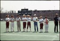 Augsburg women's softball team players with their parents on the athletic field, 1990.
