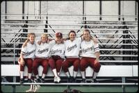 Augsburg women's softball players take a photo together on bench, May 1992