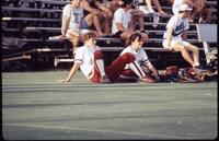 Augsburg women's softball players sitting on field, April 1992