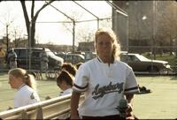 Augsburg women's softball player holding cups, April 1992