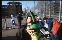 Augsburg women's tennis player holds green water bottle up to camera, April 1993