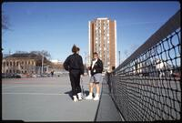 Augsburg women's tennis players talk to each other while standing on court, April 1993
