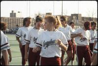 Augsburg women's softball player holds ball while surrounded by teammates, April 1992