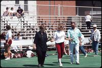 Augsburg women's softball player hands roses to people next to her, 1991