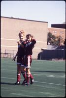 Augsburg women's soccer players walk beside each other on the field, October 1992