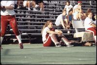 Augsburg women's softball catcher sitting on field, April 1992