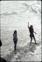 Two Augsburg women's basketball players stand in the ocean, January 1992