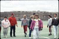 Augsburg women's softball player walks on field with unidentified people, April 1992