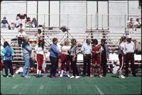Augsburg women's softball players stand on field with people, 1991