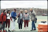 Augsburg women's softball players stand on field with unidentified people, April 1992