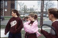 Augsburg women's tennis coach stands beside her players, 1993