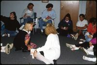 Augsburg women's basketball players sit in a circle and open Christmas presents, December 1991