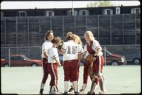 Augsburg women's softball players stand in a circle, May 1992