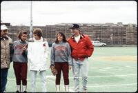 Augsburg women's softball players stand beside unidentified people, April 1992
