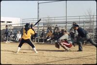 Augsburg women's softball catcher at position as rival opponent swings bat, April 1992