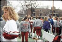 Augsburg women's softball players and unidentified people stand around bench, April 1992