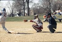 Augsburg women's softball catcher holds her mitt out, April 1992