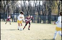 Concordia women's soccer player kicks ball as Augsburg women's soccer player tries to get it from her, October 1992