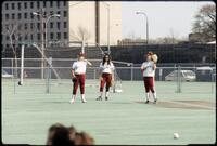 Augsburg women's softball players stand on the field, April 1992