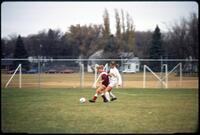 Augsburg women's soccer player kicking ball as rival player pursues her, 1991