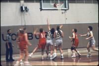 Augsburg women's basketball players reach towards net, February 1992