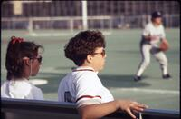 Augsburg women's softball players sitting on bench, April 1992