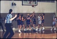 Rival women's basketball players reach for ball falling out of net, January 1992