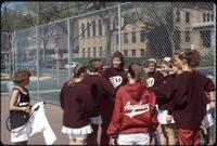 Augsburg women's tennis players huddling up with the coach, circa 1990
