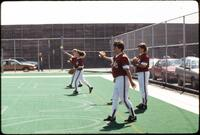 Augsburg women's softball team players warm up before a game, 1994.