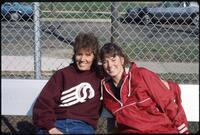 An Augsburg women's tennis team coach takes a photo with a player, circa 1985.