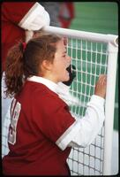 An Augsburg women's softball team player on a bench cheering on her teammates, 1995.