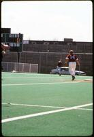 An Augsburg women's softball team outfield player throws the ball, 1975.